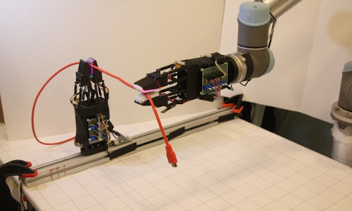 The system uses a pair of soft robotic grippers with high-resolution tactile sensors to manipulate freely moving cables.